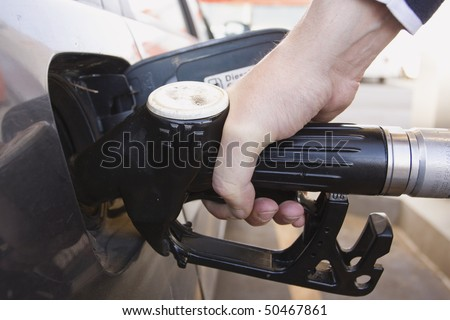 close-up of a mens hand refueling a car at a gas station (Fuel Pump) - stock photo