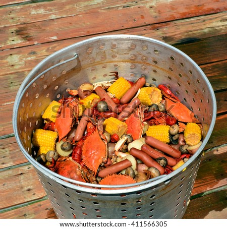 Close up of a metal basket of hot boiled crabs and crawfish with sausage, potatoes, corn on the cob, mushrooms and garlic, sitting on a wooden dock. - stock photo
