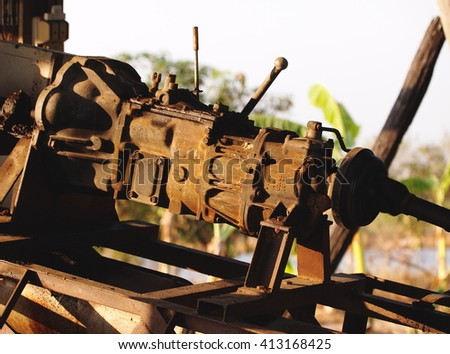 close up of a metal steel drive shaft of a water pump connected on used flywheel and gearbox from old vehicle automobile on running using in agricultural farmland in THAILAND - stock photo