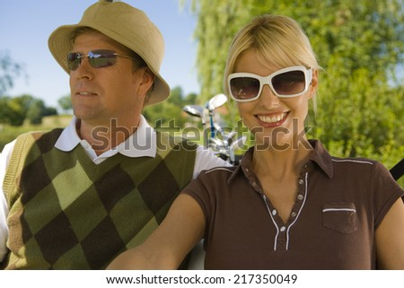 Close-up of a mid adult couple sitting in a golf cart and smiling - stock photo