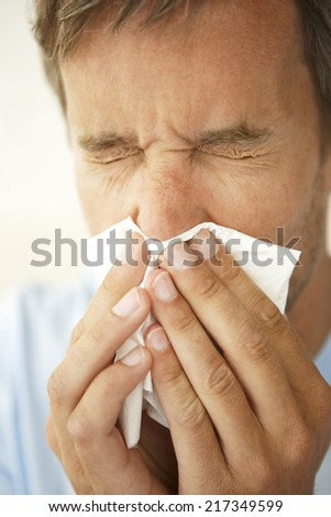 Close-up of a mid adult man sneezing - stock photo