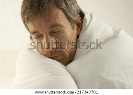 Close-up of a mid adult man wrapped in a duvet and sleeping - stock photo