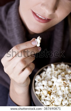 Close-up of a mid adult woman eating popcorn - stock photo
