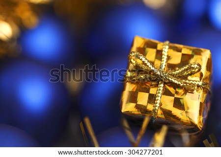 Close-up of a miniature gold gift box against a background of blue Christmas balls. Focus is on gift box.