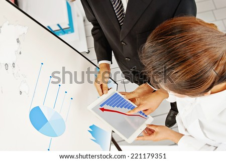 Close-up of a modern business team using tablet computer to work with financial data - stock photo