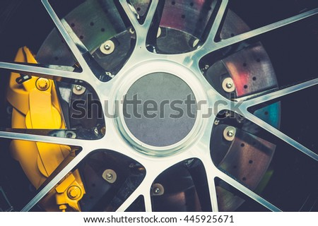 Close up of a modern sport wheel with yellow brake - stock photo