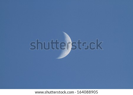 Close up of a moon with blue sky background - stock photo