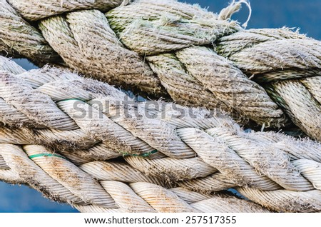 Close-up of a mooring rope with a knotted end tied around a cleat on a pier/ Nautical mooring rope - stock photo