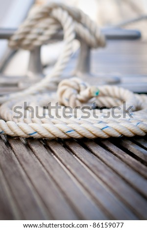 Close-up of a mooring rope with a knotted end tied around a cleat on a wooden pier/ Mooring rope - stock photo