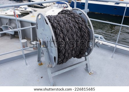 Close-up of a mooring rope with a knotted end tied around a cleat on a wooden pier. Nautical mooring rope - stock photo