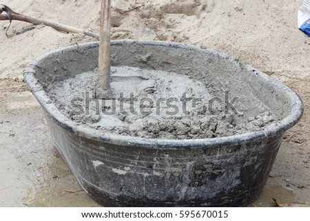 close-up of a mortar hoe mixing fresh mortar in a trough