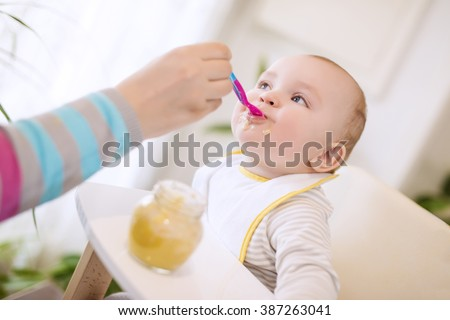 Close up of a mother feeding her baby  - stock photo