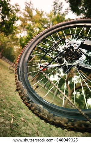 Close up of a moving mountain bicycle rear wheel with details, chain and gearshift mechanism.