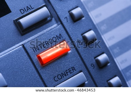 Close up of a multi-line business telephone with a lit intercom button. Horizontal shot. - stock photo