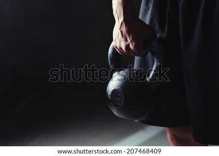 Close-up of a muscular hand holding a kettlebell - stock photo