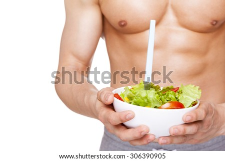Close-up of a muscular man holding a bowl of salad, isolated on white background - stock photo