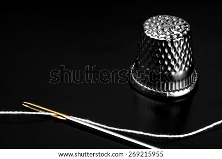 Close up of a needle eye with white thread - stock photo