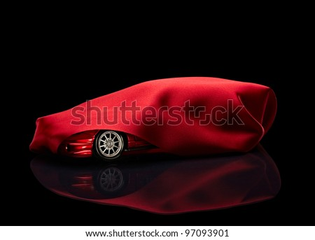 close up of  a new car hidden under red cover on black background - stock photo