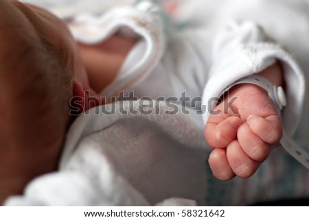 Close up of a newborn infants baby hand and wristband shortly after birth. Shallow depth of field. - stock photo