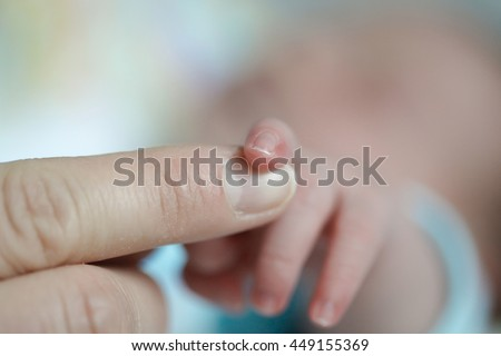 Close-up of a newborns finger touching mothers hand. Innocence, security, purity, motherhood, new life, love and happiness concept. 