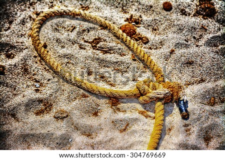 close up of a noose on the sand in hdr tone mapping effect - stock photo