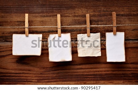 close up of  a note paper and clothes peg on a wooden background - stock photo