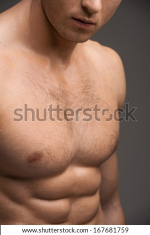 Close up of a nude man muscular chest. Standing isolated over grey background  - stock photo