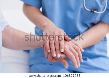 Close up of a nurse touching hand of a patient in hospital ward - stock photo