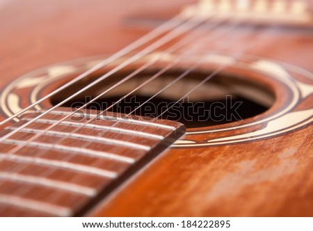 Close up of a old used brown western guitar.Picture is toned. - stock photo