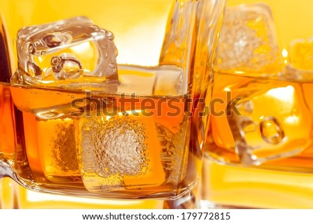 close-up of a pair of glasses of whiskey with ice on yellow background - stock photo