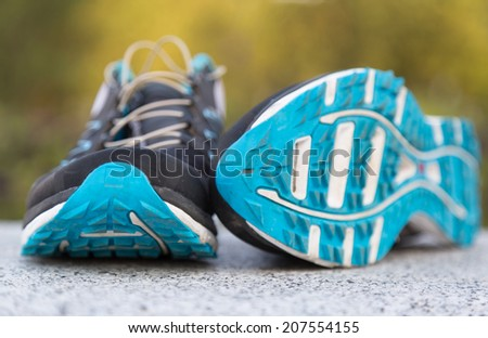 Close up of a pair of trail running shoes in a park. - stock photo