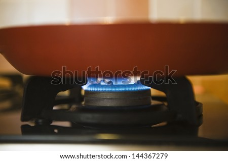 Close-up of a pan on a gas stove burner - stock photo