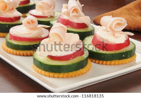 Close up of a party plate of canapes with cucumbers and turkey - stock photo