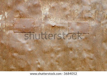 Close-up of a patched rusty metal plate - stock photo