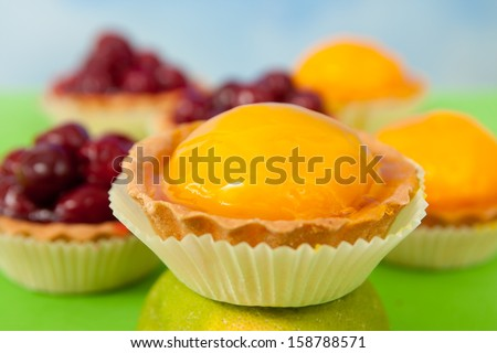 Close up of a peach tart with jelly in colorful surrounding