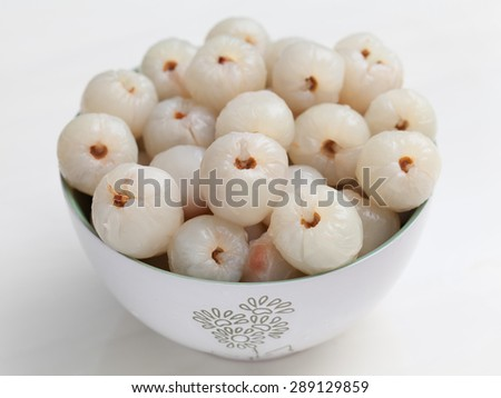 Close up of a peepled lychee in a bowl on white background. - stock photo