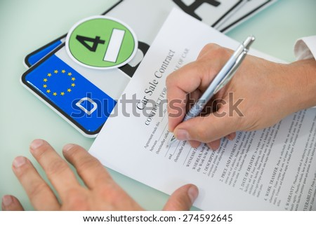 Close-up Of A Person Filling Car Sale Contract Form With Number Plate On Desk. Contract Paper Contains Placeholder Text - stock photo