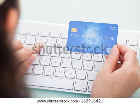Close-up Of A Person Holding Credit Card Using Laptop - stock photo