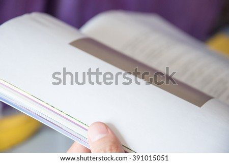 Close-up of a person holding opened book.