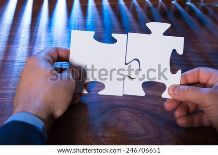 Close-up Of A Person Joining Two Jigsaw Pieces On Desk - stock photo