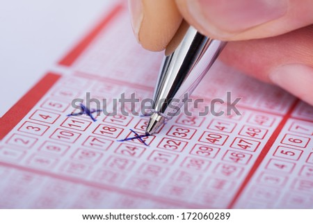 Close-up Of A Person Marking Number On Lottery Ticket With Pen - stock photo