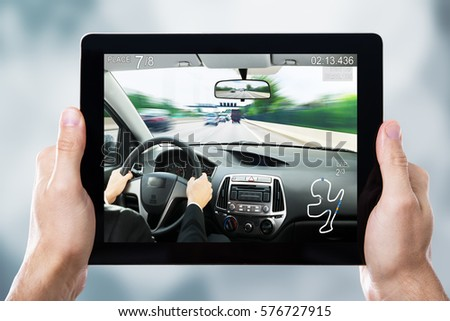 Close-up Of A Person Playing Car Racing Game On Digital Tablet