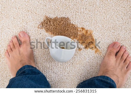 Close-up Of A Person's Feet Standing Near Coffee Spilled On Carpet - stock photo