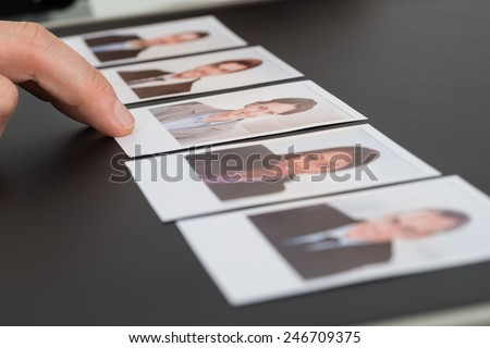 Close-up Of A Person's Hand Choosing Photograph Of A Candidate - stock photo