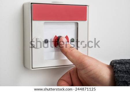 Close-up Of A Person's Hand Pressing Emergency Alarm Button - stock photo