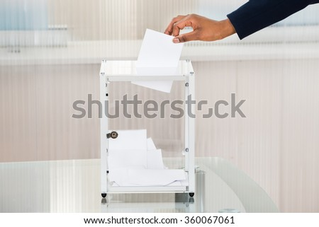 Close-up Of A Person's Hand Putting Ballot In Box - stock photo