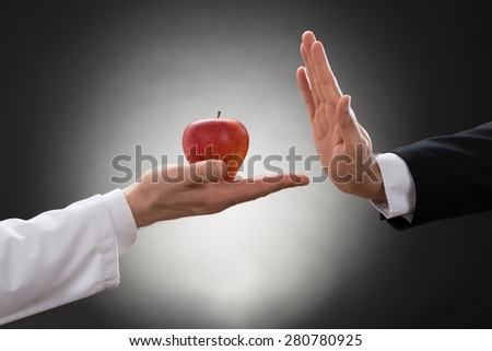 Close-up Of A Person's Hand Refusing Red Apple Held By Doctor