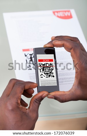 Close-up Of A Person's Hand Scanning Barcode With Cellphone - stock photo