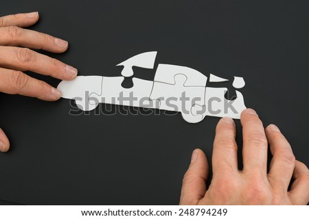 Close-up Of A Person's Hand Solving Car Jigsaw Puzzle - stock photo