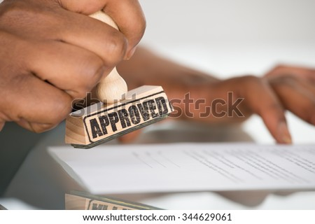 Close-up Of A Person's Hand Stamping On Approved Contract Form - stock photo